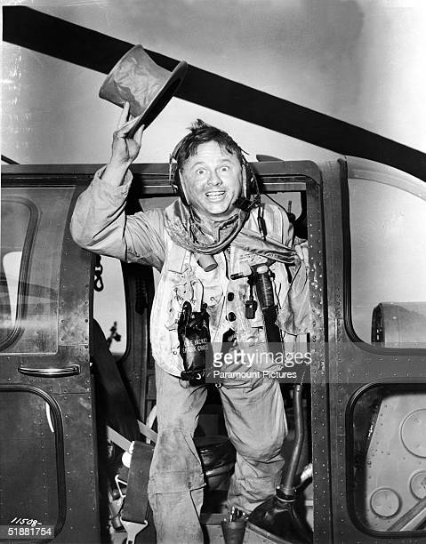 American actor Mickey Rooney waves a tophat and smiles from the door of a helicopter as maverick pilot 'Mike Forney' in 'The Bridges at TokoRi'...