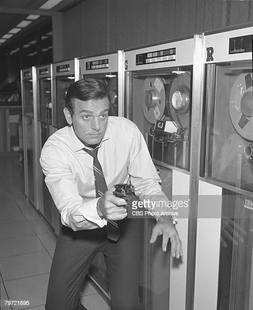 American actor Mike Connors as Joe Mannix aims his gun in a room full of computers in a scene from the pilot episode of the television detective...