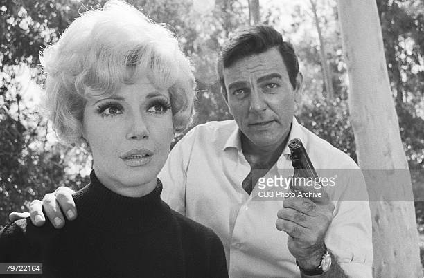 American actor Mike Connors as Joe Mannix and Canadian actress Ruta Lee in the woods in a scene from an episode of the television detective series...