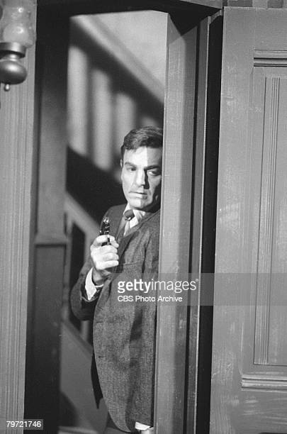 American actor Mike Connors as Joe Mannix cautiously peers around a doorframe in an episode of the television detective series 'Mannix' entitled 'A...