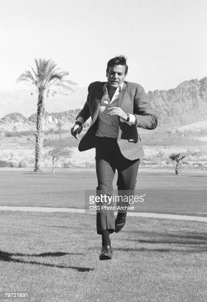 American actor Mike Connors as Joe Mannix runs across a field in a scene from the pilot episode of the television detective series 'Mannix' December...