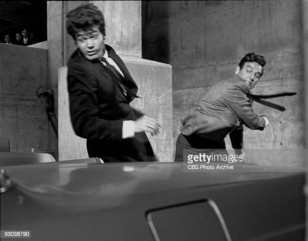 American actor Mike Connors as private detective Joe Mannix in midswing after punching an unidentifed assailant during an episode of 'Mannix' 1967