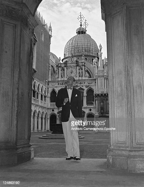 American actor Mische Auer wearing a blazer and a bow tie and holding a cigarette portrayed while visiting the court of the Doge's Palace Venice 1949