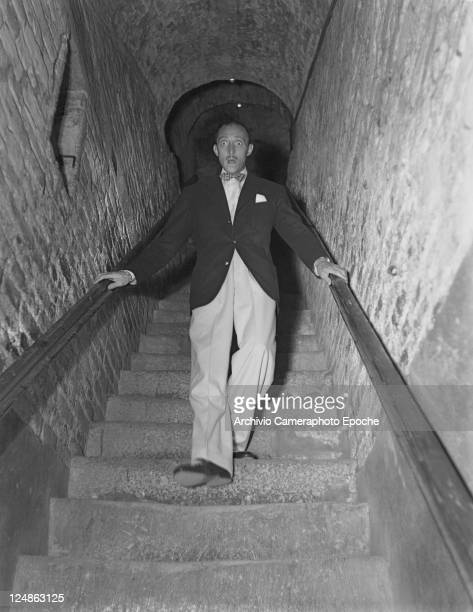 American actor Mische Auer wearing a blazer and a bow tie portrayed while descending stairs Venice 1949