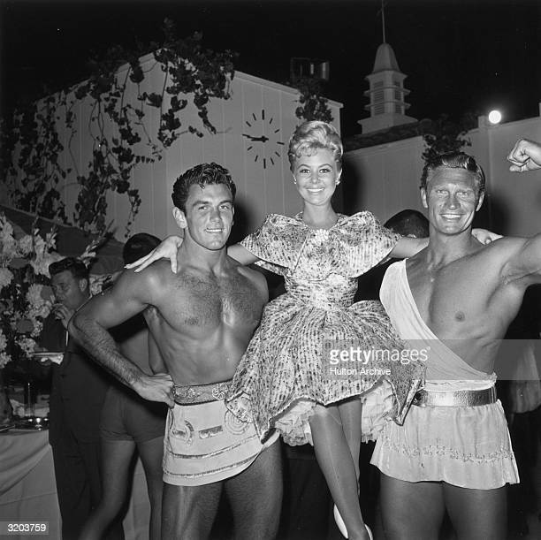 American actor Mitzi Gaynor smiles while being carried by two muscular men in toga costumes outdoors at a party for the premiere of director Pietro...