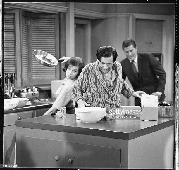 American actor Morey Amsterdam cooks breakfast in the kitchen accompanied by American actors Mary Tyler Moore and Dick Van Dyke in a scene from an...