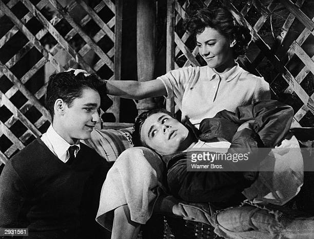 American actor Natalie Wood sits with her hand on the head of American actor Sal Mineo and American actor James Dean in her lap in a scene from...