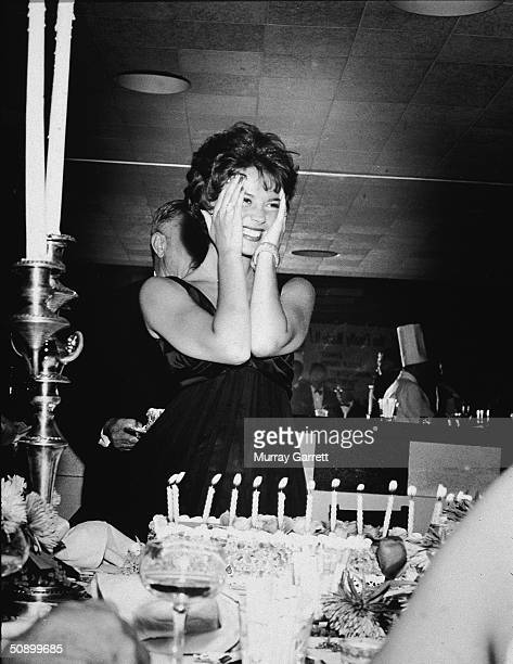 American actor Natalie Wood smiles and holds her hands to her face standing behind her birthday cake during her surprise 21st birthday party...
