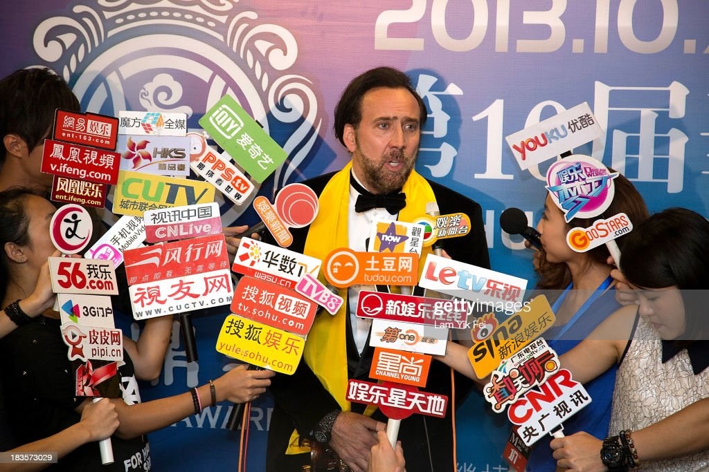 American actor Nicolas Cage (C) speaks to the media after winning Best Global Actor in Motion Picture at the 2013 Huading Awards ceremony at The Venetian on October 7, 2013 in Macau, Macau.
