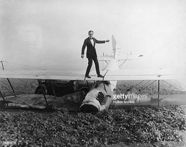 American actor Ormer Locklear wearing a tuxedo walks on the wings of an airplane crashed in a farmer's field in a still from director James P Hogan's...