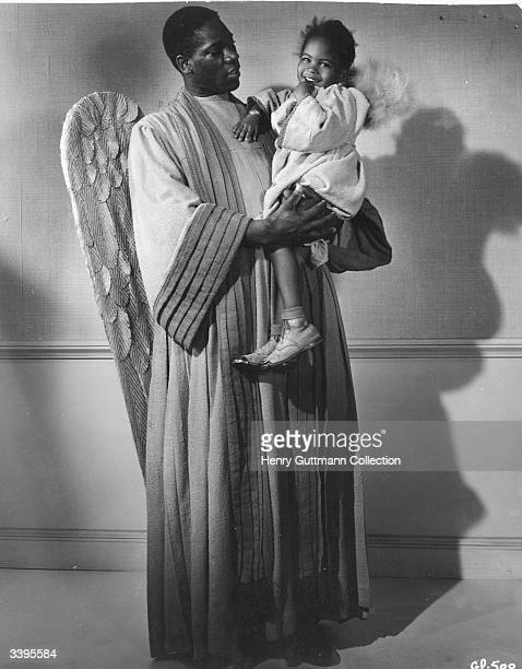 American actor Oscar Polk as the Archangel Gabriel holding a child dressed as an angel in the film 'Green Pastures' a retelling of the Old Testament...