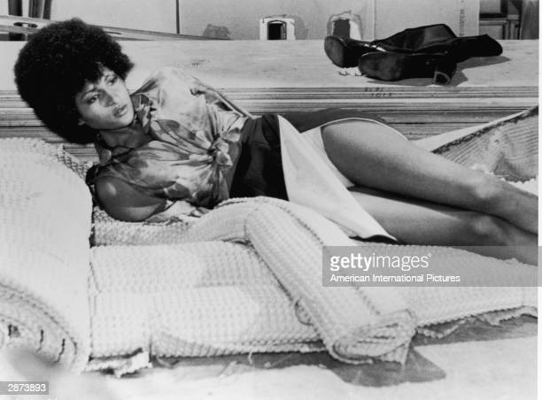 American actor Pam Grier lays on a mat with her hands tied behind her back, in a still from 'Foxy Brown,' directed by Jack Hill, 1974.