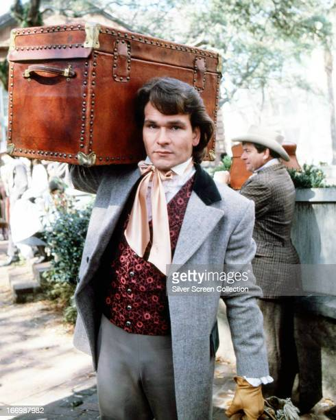 American actor Patrick Swayze carrying a trunk as Orry Main in the TV miniseries 'North And South' 1985