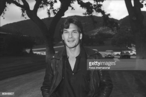American actor Patrick Swayze smiles as he poses in a leather jacket at a charity auction of Arabian horses for AIDS research on the grounds of...