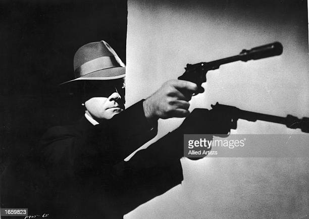 American actor Paul Dubov wearing fedora points a gun outfitted with a silencer while casting a shadow against a wall in a still from the film 'The...