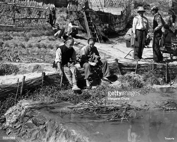 American actor Paul Muni and actress Luise Rainer prepare to shoot a farm scene for the film 'The Good Earth'