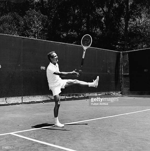 American actor Paul Newman throws his racket in the air jokingly while playing tennis, 1960s.