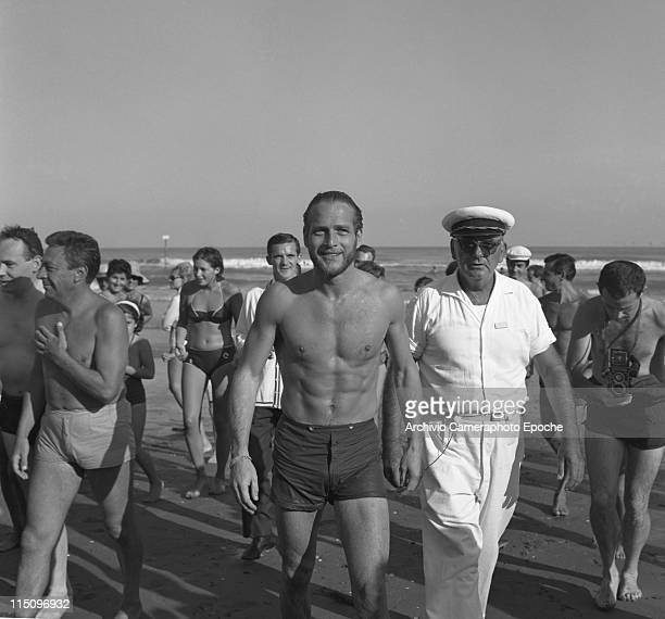 American actor Paul Newman wearing a swimming suit walking on the Lido seashore surrounded by the crowd a man wearing a sailor cap and another one...