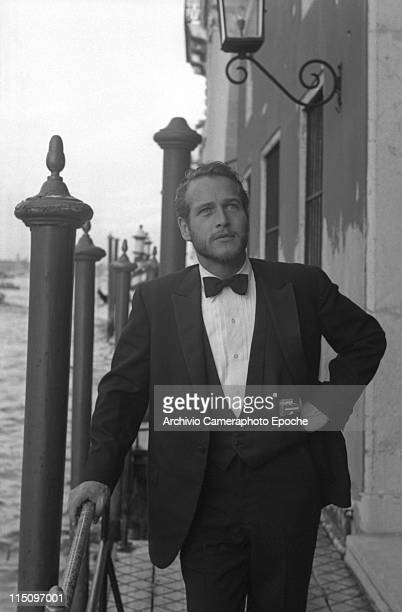 American actor Paul Newman wearing a tuxedo and a bow tie a pack of Red Marlboro cigarettes in his pocket a hand on the hip some hooden poles behind...