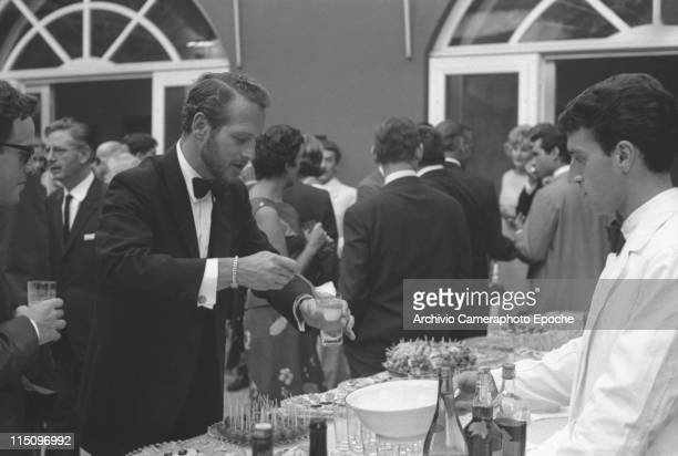 American actor Paul Newman wearing a tuxedo and a bow tie standing behind a buffet and putting ice in a glass with a drink many people around him a...