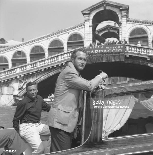 American actor Paul Newman wearing trousers a blazer and a scarf standing on a water taxi surrounded by men under Rialto Bridge Grand Canal Venice...