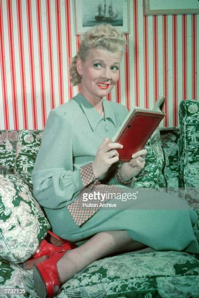 American actor Penny Singleton poses on a couch with a book circa 1945