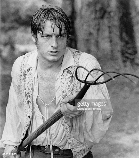 American actor Perry King holding a pitchfork in the film Mandingo 1975
