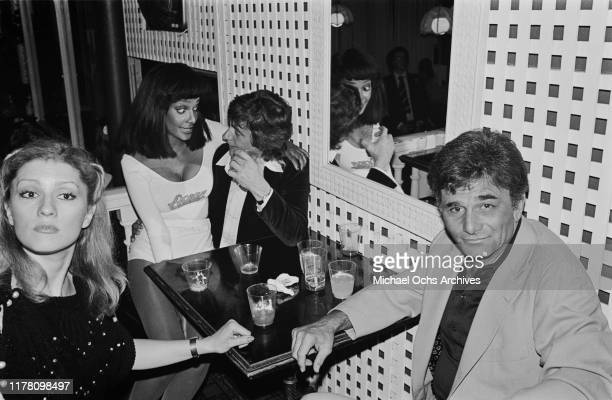 American actor Peter Falk with his wife actress Shera Danese and between them English actor Dudley Moore with a party hostess at a launch party for...