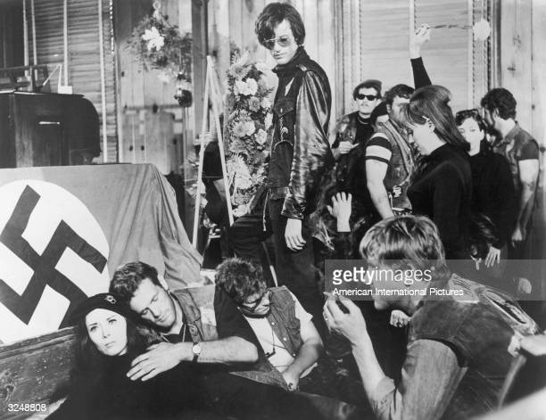 American actor Peter Fonda and and other hippies hang out in front of a podium with a Nazi swastika flag in a still from the film 'The Wild Angels'...