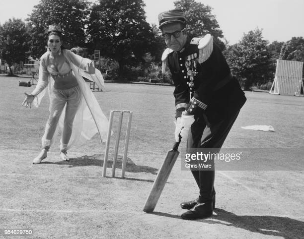 American actor Phil Silvers and English actress Anita Harris filming a cricket scene for the Carry On film 'Follow That Camel' at Pinewood Studios UK...