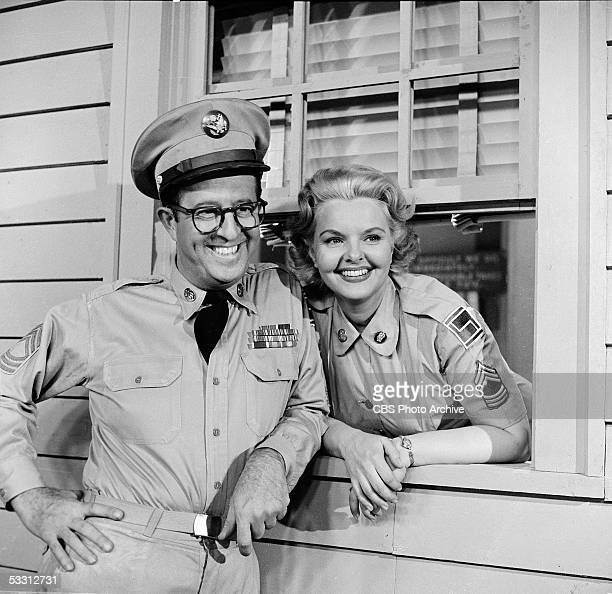 American actor Phil Silvers leans against a window sill as American actress Elisabeth Fraser looks out the window in an episode of the TV comedy...
