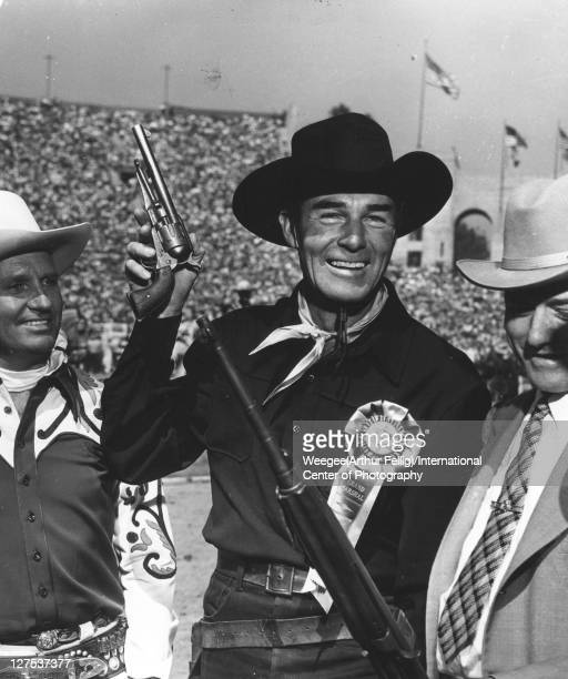 American actor Randolph Scott dresssed as cowboy with a pistol on on hand smiles along with unidentified others as they stand in Los Angeles Memorial...