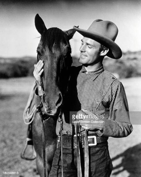 American actor Randolph Scott posing with a horse in a western role circa 1935