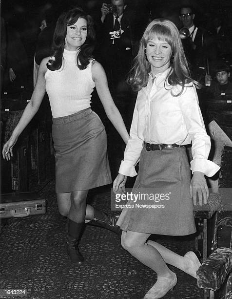 American actor Raquel Welch and British actor Julie Christie practice curtsying for their presentation to Queen Elizabeth II during a Royal Film...