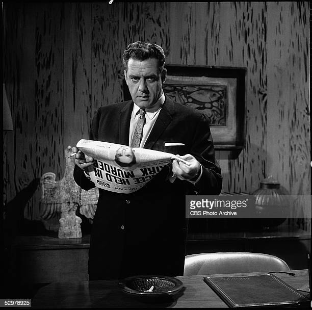 American actor Raymond Burr in character as crimesolving lawyer Perry Mason looks up from a newspaper as he smokes and stands behind a desk in a...