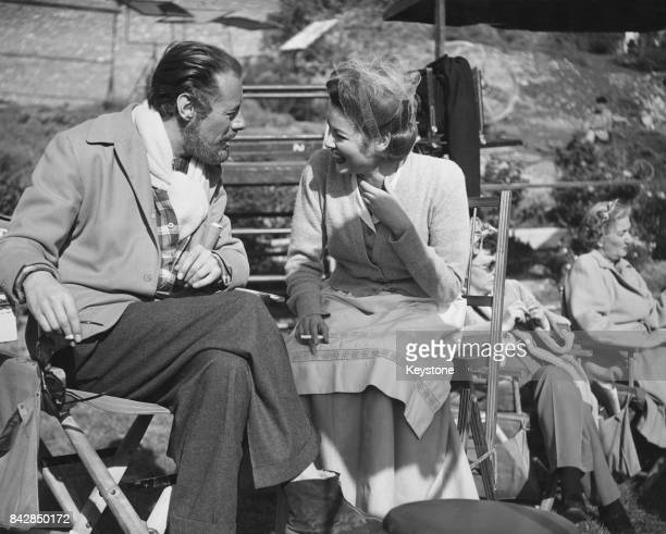 American actor Rex Harrison laughing with costar Gene Tierney during the filming of 'The Ghost and Mrs Muir' 1947 Production has been delayed by...