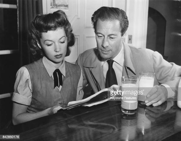 American actor Rex Harrison reading a script with his wife, actress Lilli Palmer over glasses of milk, May 1948.