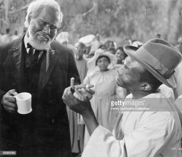 American actor Rex Ingram as De Lawd being offered a cigar during a scene from the film 'Green Pastures' a retelling of the Old Testament stories...