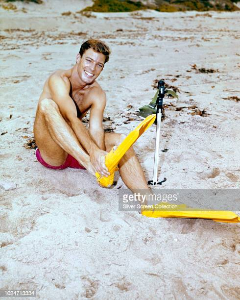 American actor Richard Chamberlain puts on his flippers before a swim circa 1965