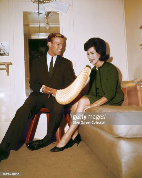 American actor Richard Chamberlain shows actress Michele Lee a jai alai glove or 'cesta' circa 1965