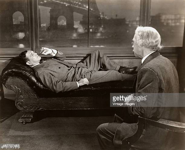 American actor Richard Dix as private detective Don Gale, reclining against a New York City backdrop in a scene from the Columbia Pictures film...