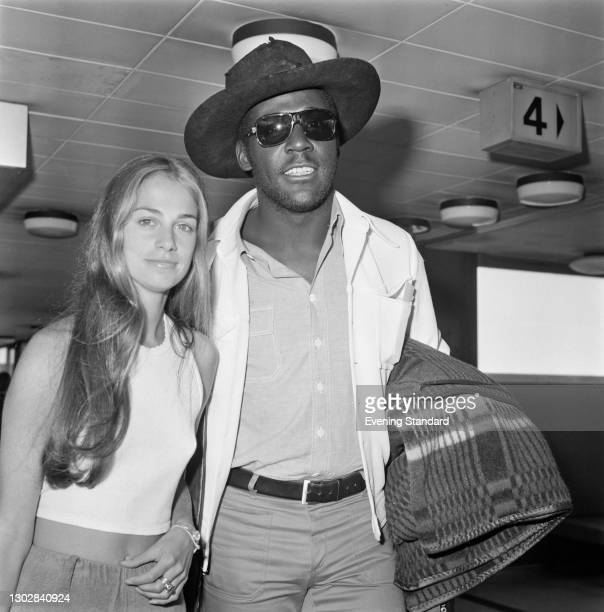 American actor Richard Roundtree at Heathrow Airport in London, with a young woman, UK, 25th July 1972.