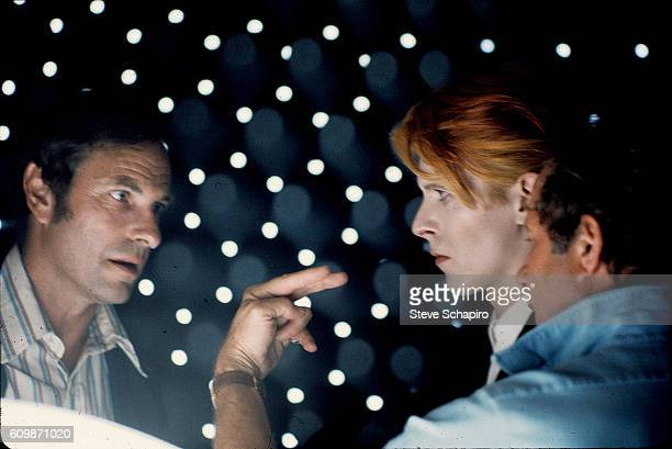 American actor Rip Torn and English musician and actor David Bowie stare at one another as director Nicolas Roeg getures on the set of their film...