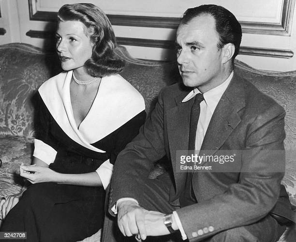 American actor Rita Hayworth and her third husband Prince Aly Khan of Pakistan sit next to each other on a sofa during a press conference to announce...