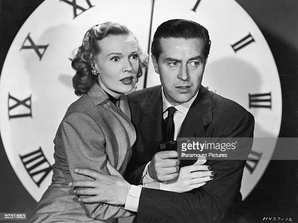 American actor Rita Johnson and Welshborn actor Ray Milland holding a gun embrace in front of a large clock face in a still from director John...