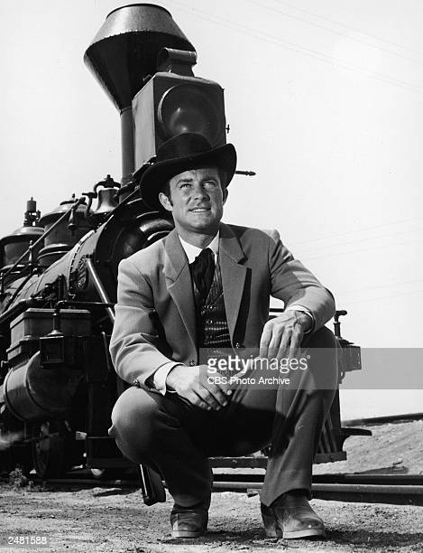 American actor Robert Conrad crouches in front of a steam locomotive in a promotional still for the television series 'The Wild Wild West' circa 1966