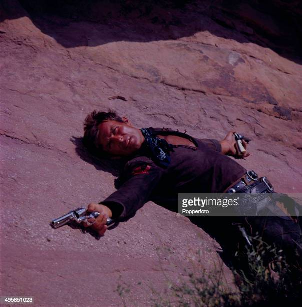 American actor Robert Conrad pictured holding a revolver in each hand on the set of the television series 'The Wild Wild West' in 1968