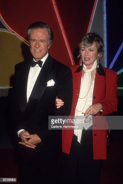 American actor Robert Culp and his wife, Candace Faulkner, stand in front of a neon sign for NBC-TV. Culp wears a tuxedo.