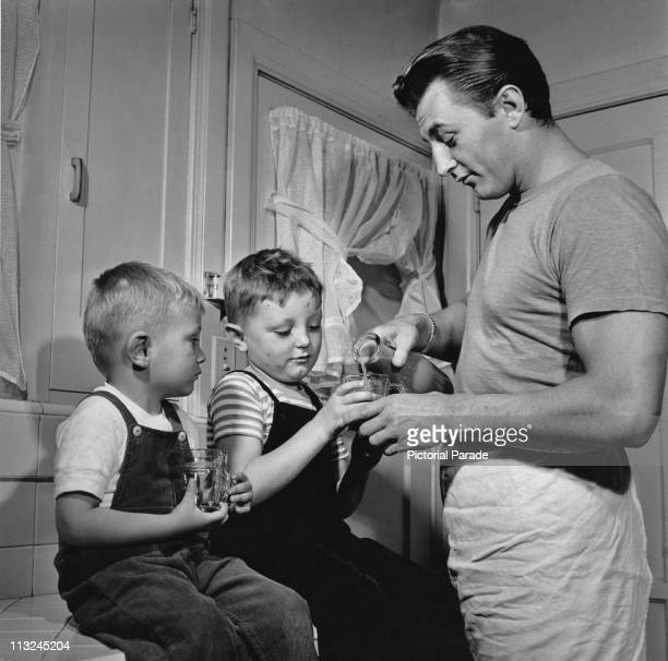 American actor Robert Mitchum at home with his sons Christopher and James circa 1946