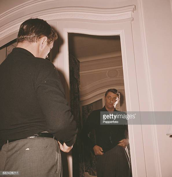 American actor Robert Mitchum pictured looking at a mirror in a London hotel in 1963
